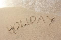 "Stock Photo of sand beach with ""holiday"" word"