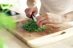 Woman slicing basil on chopping board in kitchen,slow motion shot at 240fps NTSC Stock Footage