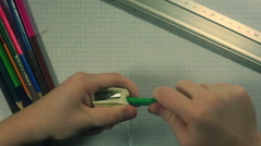 Child's hands sharpening a green pencil Stock Footage