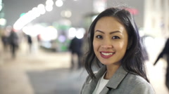 Portrait of smiling professional woman in city at night with crowds and traffic  - stock footage