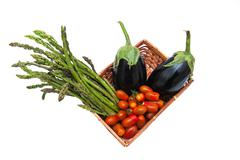 Basket with bunch of asparagus, tomato and aubergines isolated - stock photo