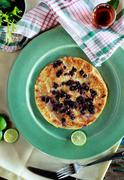 blueberry pancake on green plate served with maple syrup - stock photo