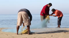 Fishermen tying fishing net on shore in Goa. - stock footage