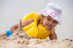 Five year old girl on the beach sand built tower - stock photo