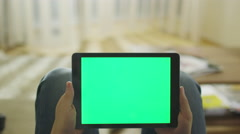 Man is Laying on Couch at Home and Holding Tablet with Green Screen in Landscape - stock footage