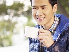 Asian young man enjoying coffee Stock Photos