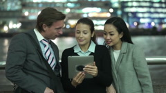 Portrait of attractive professional group using computer tablet in city at night Stock Footage