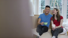 4K Young couple take a coffee break from unpacking boxes in new home - stock footage