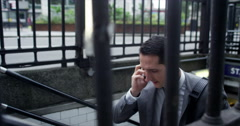 4K London businessman talking on phone as he emerges from underground station - stock footage