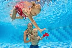 Baby underwater swimming lesson with instructor in the pool - stock photo