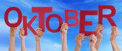 People Holding Word Oktober Means October Blue Sky - stock photo