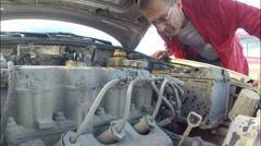 Man under the hood of a broken car Stock Footage