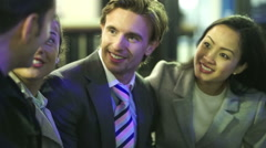 Attractive young professional group chatting and laughing in the city at night Stock Footage
