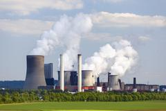 A coal-fired power station in the distance in agricultural landscape. The pow - stock photo