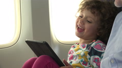 Small girl using tablet on an airplane Stock Footage