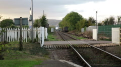 Steam train distant smoke & level crossing, England Stock Footage
