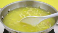 Stirring chicken noodle soup in skillet Stock Footage