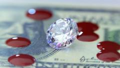 Diamond, money and falling drops of blood. Closeup Stock Footage