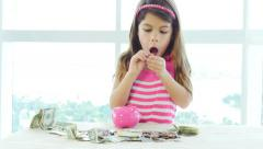 Little girl shows us a coin and piggybank Stock Footage