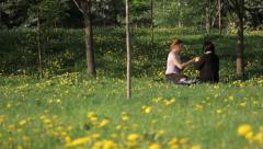 Two girls in the Park sitting on the grass Stock Footage