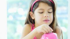 Close-up of little girl and her piggybank - stock footage