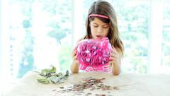 Little girl emptying her pink piggy bank - stock footage