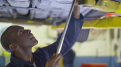 4K Mechanic working underneath a car in garage workshop Stock Footage