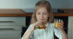 Child drinking orange juice and eating a sandwich - stock footage