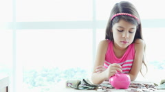 Serious little girl in pink places coins into her piggybank Stock Footage