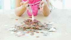 Close-up of little girl putting coins in piggybank - stock footage