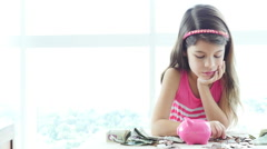 Serious little girl places coins and bills into her piggybank. - stock footage