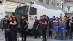 Police wearing full equipment belt wait against demonstrators on Istiklal Street - stock footage