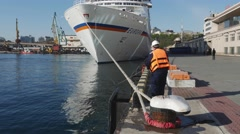 Timelapse of port worker help to dock the big white cruise liner Stock Footage