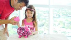 Little girl and her dad placing coins into piggybank - stock footage