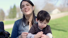 Mother and son sitting outside on a spring day HD Stock Footage
