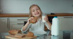 Stock Video Footage of Portrait of a girl preschooler in the kitchen. Girl holding a sandwich