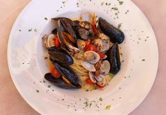 Italian pasta with fresh shellfish sauce in white plate - stock photo