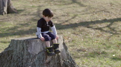 Boy sits on a tree stump and waves his legs around HD Stock Footage