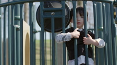 Boy looking through railings at a park 4K Stock Footage