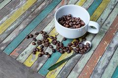 Coffee beans in a cup on the color table wood - stock photo