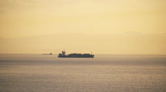 Long shot,telephoto, container ship on the horizon at sunset. Stock Footage