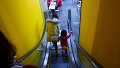Mother and baby come out of escalator in basement restaurant of Shilin Market Stock Footage