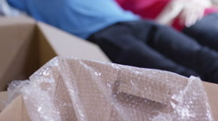 4K Happy affectionate young couple lying amongst cardboard boxes in new home - stock footage