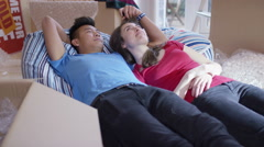 4K Happy affectionate young couple lying amongst cardboard boxes in new home Stock Footage