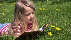 4K Child, Little Girl Reading a Storybook in Park, Kid Playing Book Meadow Grass - stock footage
