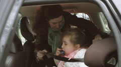 Mother fastening girl's seat belt Stock Footage