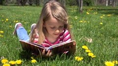 4K Child Little Girl Reading a Storybook in Park, Kid Playing Book Meadow Grass Stock Footage