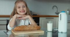 Portrait of a girl preschooler in the kitchen with a loaf of bread - stock footage