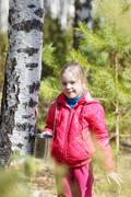 Little girl collects birch sap in woods Stock Photos