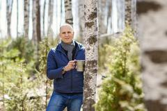Man in woods collecting birch sap - stock photo